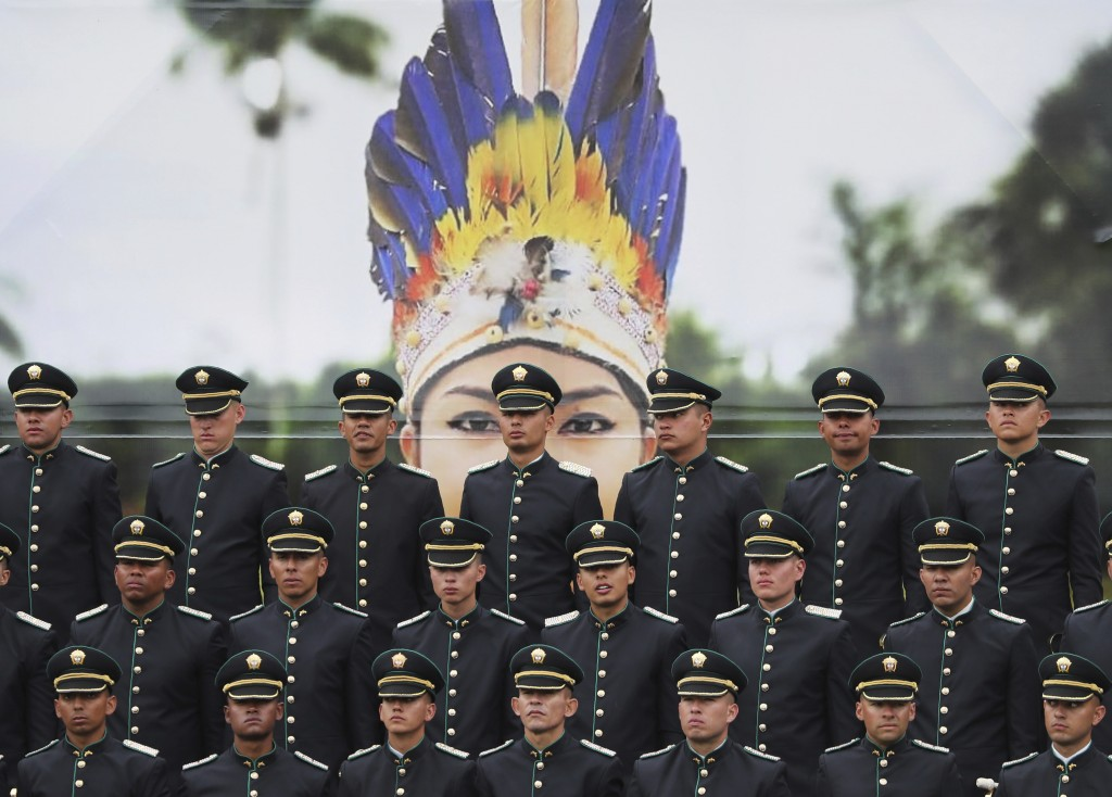Newly graduated police cadets stand in formation in front of a large photograph of an indigenous police officer, during their graduation ceremony in B...