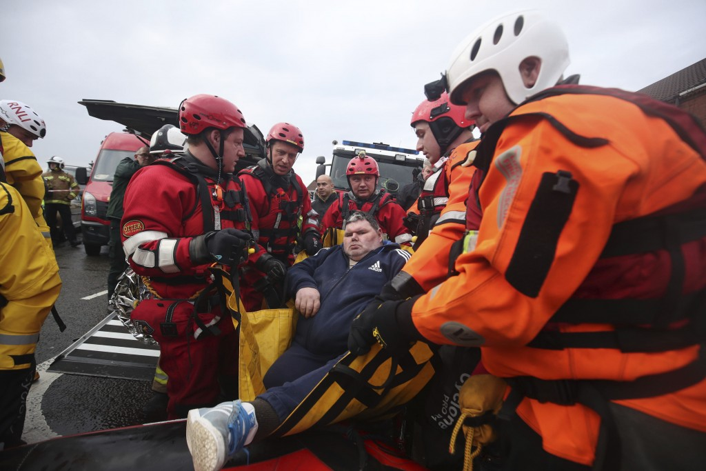 Fire and Rescue service members lift a man onto an inflatable boat that has been used to rescue residents trapped by floodwater in in Doncaster, north...