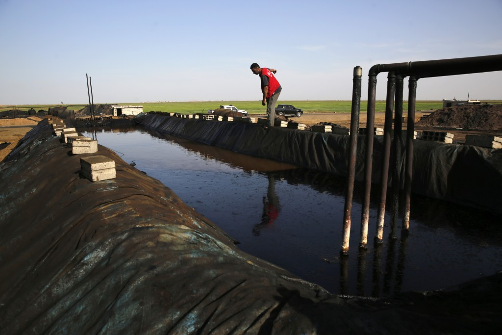 FILE - In this April 6, 2018 file photo, shows a former farmer working at a primitive refinery making crude oil into diesel and other products, in a v...