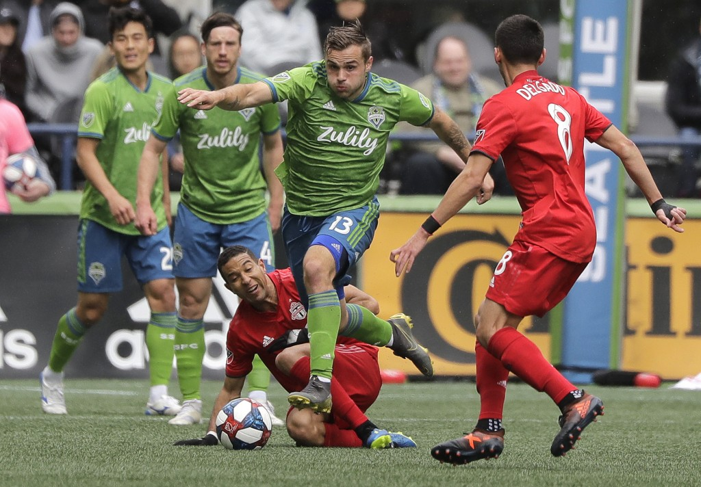FILE - In this April 13, 2019, file photo, Seattle Sounders forward Jordan Morris (13) leaps over Toronto FC defender Justin Morrow, lower center, as ...
