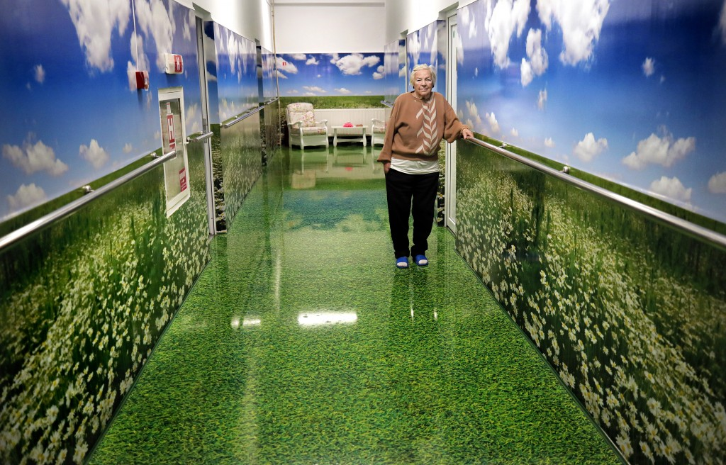 FILE- In this file photo dated Sunday, Oct. 20, 2019, an elderly woman stands in the corridor of a retirement home during a visit by Romanian presiden...