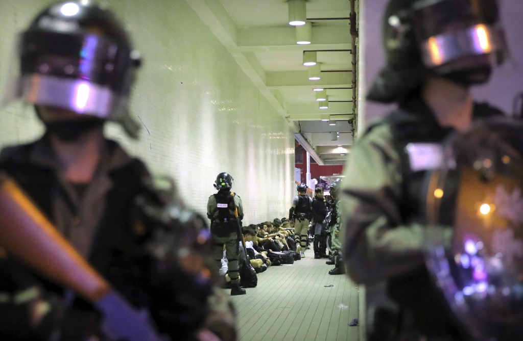 In this Saturday, Nov. 2, 2019, file photo, police in riot gear stand over people detained during a protest in Hong Kong. Hong Kong riot police fired ...