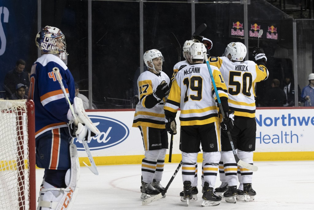 New York Islanders goaltender Semyon Varlamov stands in front of the net as the Pittsburgh Penguins celebrate after a goal by center Evgeni Malkin (71...