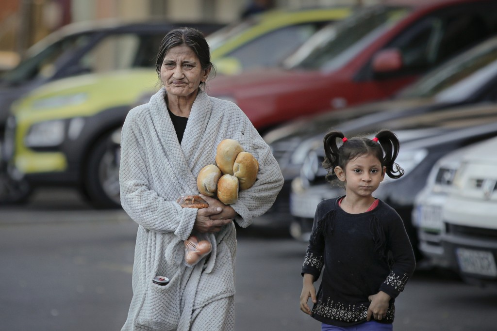 FILE- In this Sunday, Oct. 27, 2019 file picture a woman clutching loafs of bread and some eggs walks along with a child by a cleaning facility during...