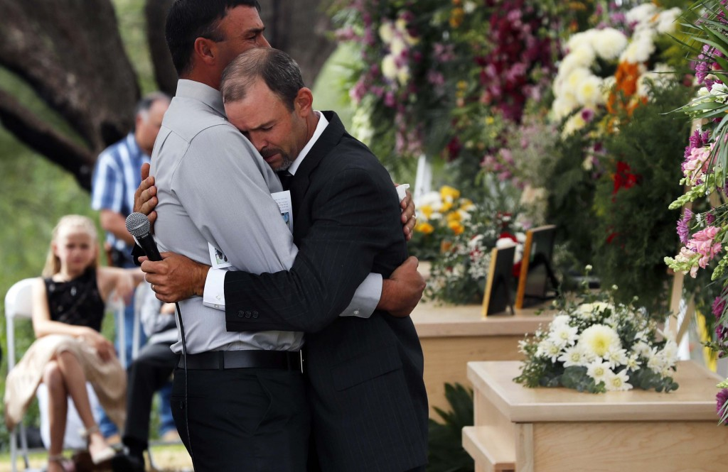 Men embrace next to the coffins of Dawna Ray Langford, 43, and her sons Trevor, 11, and Rogan, 2, who were killed by drug cartel gunmen, during the fu...