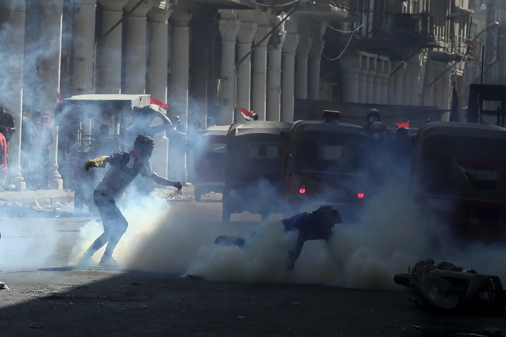 Iraqi riot police fire tear gas to disperse anti-government protesters during ongoing protests in Baghdad, Iraq, Friday, Nov. 8, 2019. (AP Photo/Hadi ...