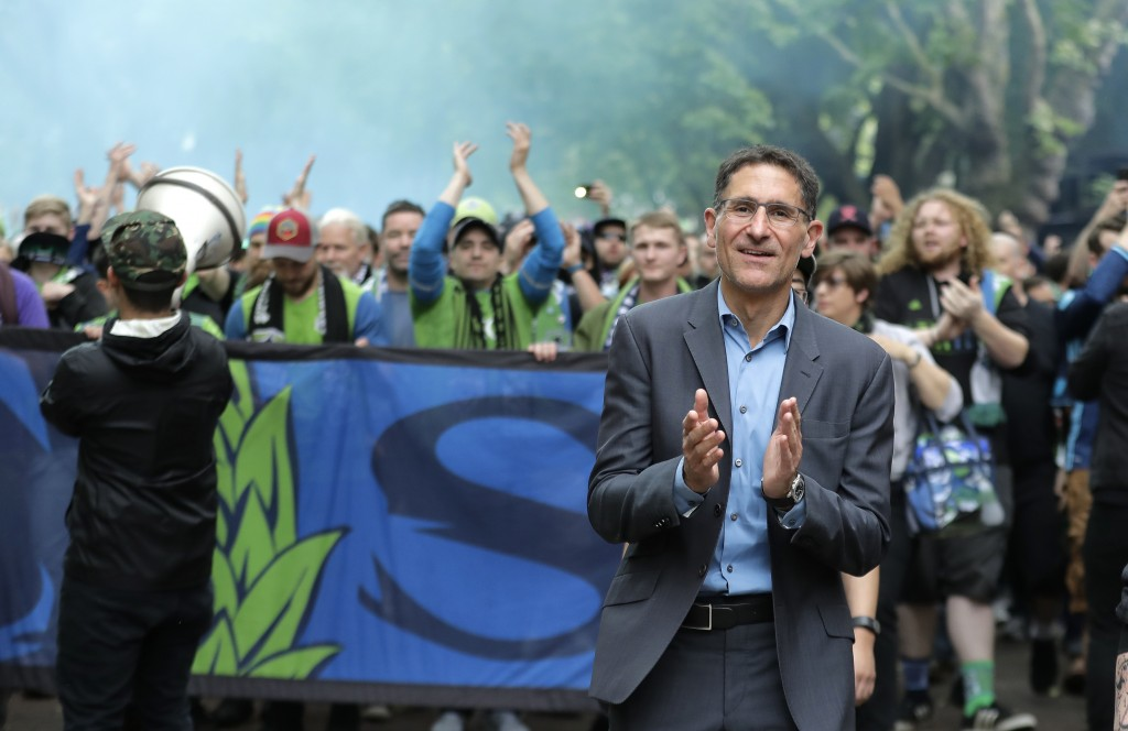 FILE - In this June 30, 2018, file photo, Seattle Sounders owner Adrian Hanauer, right, takes part in the traditional March to the Match before an MLS...