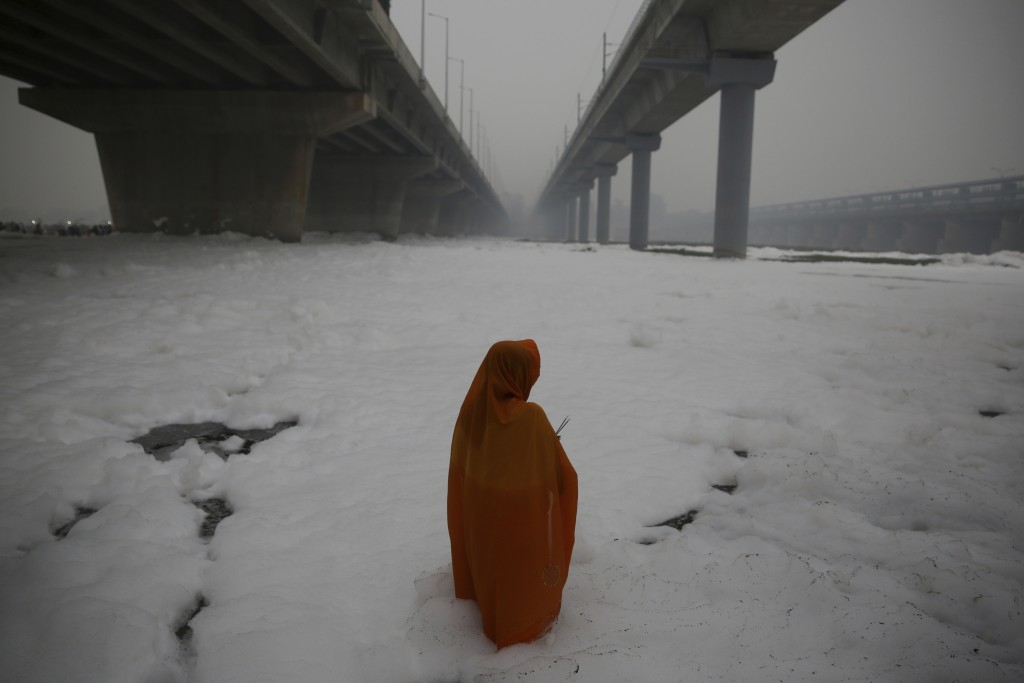 In this Saturday, Nov. 2, 2019, file photo, an Indian Hindu devotee performs rituals in Yamuna river, covered by chemical foam caused due to industria...