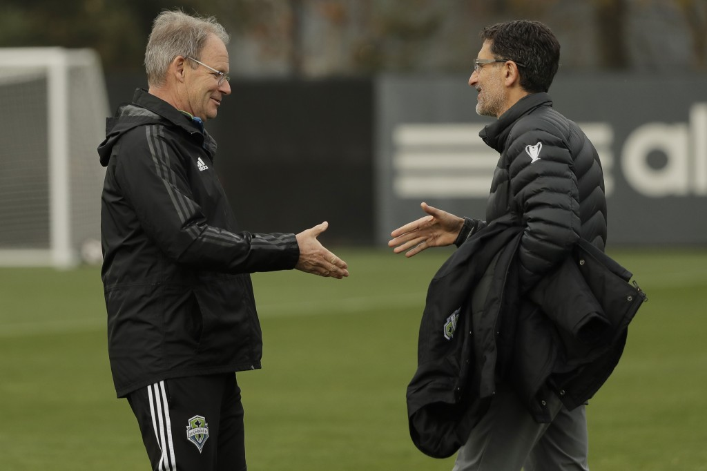 Seattle Sounders head coach Brian Schmetzer, left, shakes hands with team owner Adrian Hanauer, right, at the start of a training session, Thursday, N...