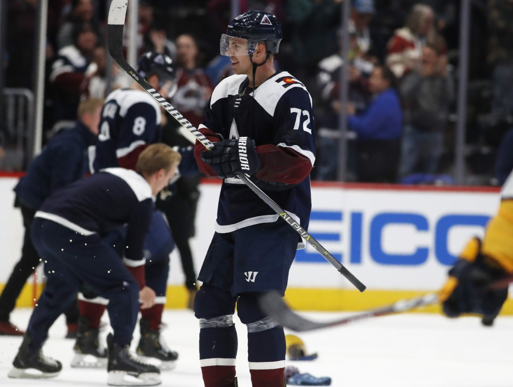 Colorado Avalanche right wing Joonas Donskoi, front, celebrates his hat trick as skaters pick up caps tossed onto the ice late in the third period of ...