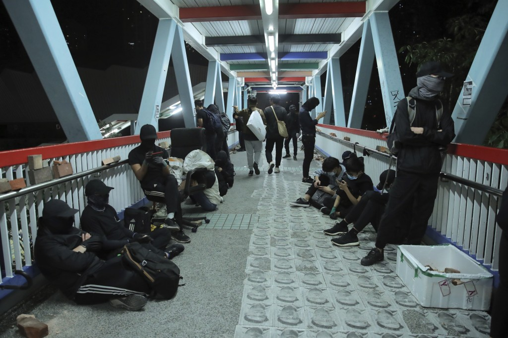 Protesters rest on a bridge in Hong Kong, early Saturday, Nov. 9, 2019. A Hong Kong university student who fell off a parking garage after police fire...