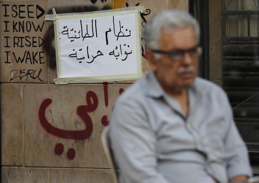 "In this Thursday, Nov. 7, 2019, an anti-government protester sits in front of an Arabic placard that reads, ""Sectarian system its lawmakers are thieve..."