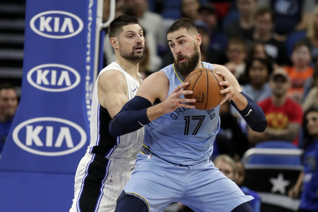 Memphis Grizzlies' Jonas Valanciunas (17) makes a move to the basket against Orlando Magic's Nikola Vucevic, left, during the first half of an NBA bas...