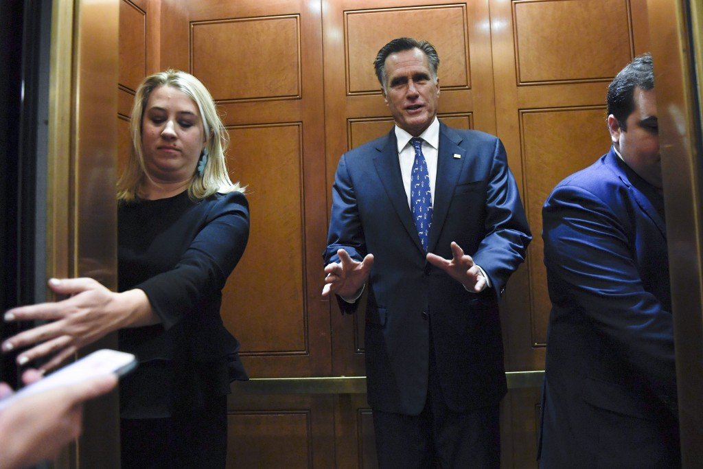 FILE - In this Nov. 5, 2019, file photo, Sen. Mitt Romney, R-Utah, gets in an elevator as he is followed by reporters on Capitol Hill in Washington. R...