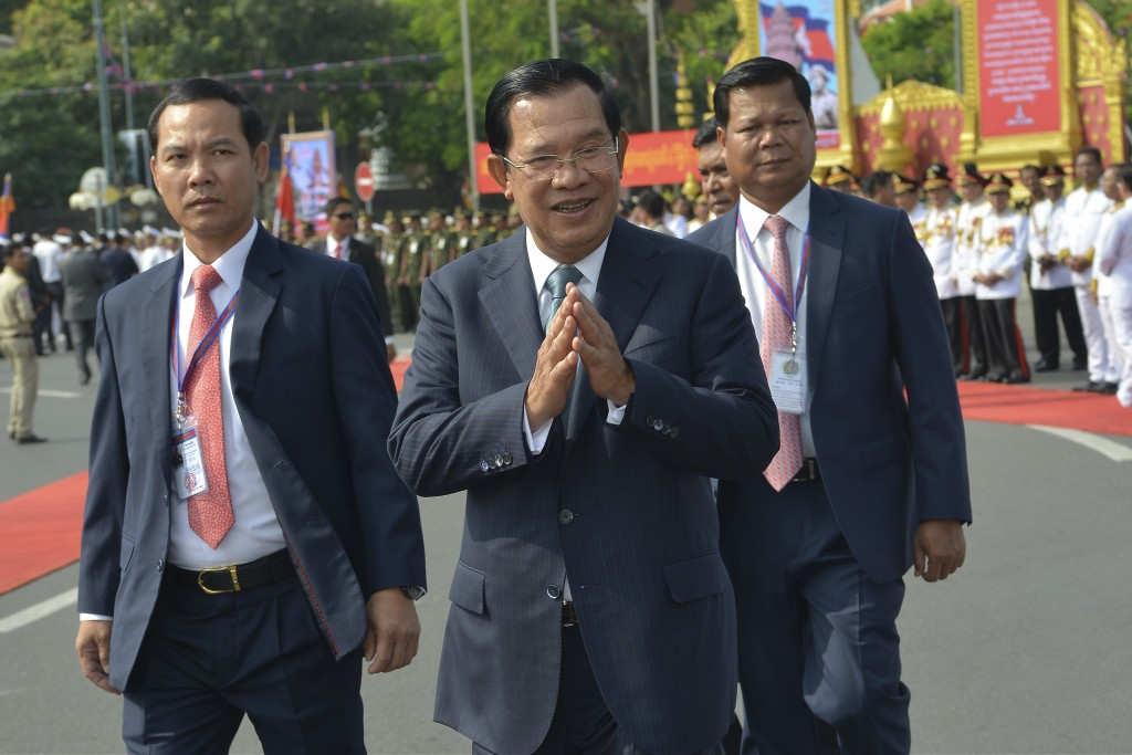 Cambodian Prime Minister Hun Sen, center, greets his government officers during the country's 66th Independence Day from France, at the Independence M...
