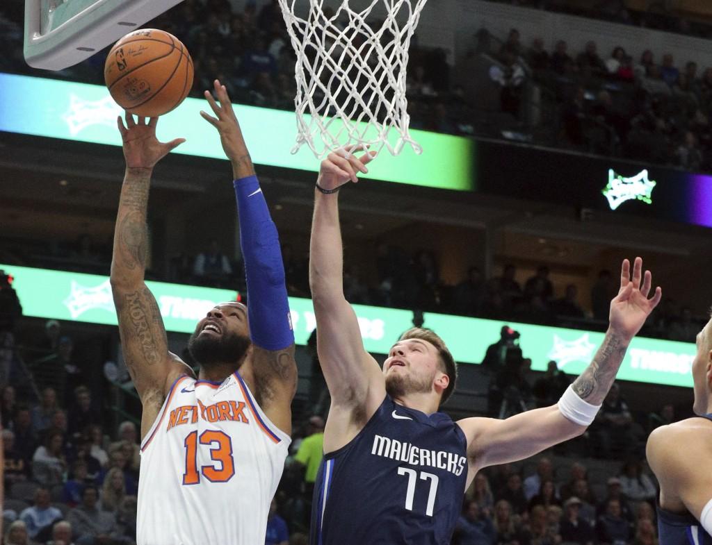New York Knicks forward Marcus Morris Sr. (13) puts up a shot against Dallas Mavericks guard Luka Doncic (77) in the first half of an NBA basketball g...