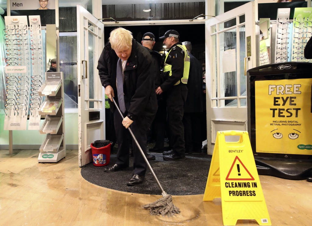 Britain's Prime Minister Boris Johnson visits an optician shop after flooding, in Matlock, north England, Friday Nov. 8, 2019. A woman died after bein...