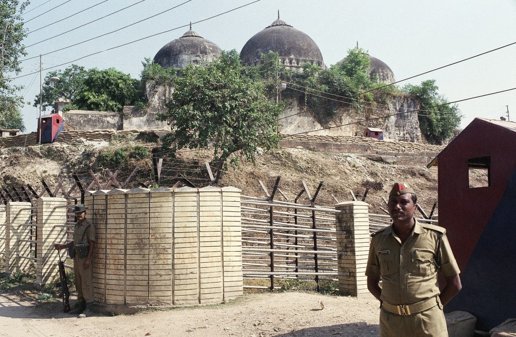 FILE - In this Oct. 29, 1990, file photo, Indian security officer guards the Babri Mosque in Ayodhya, closing off the disputed site claimed by Muslims...