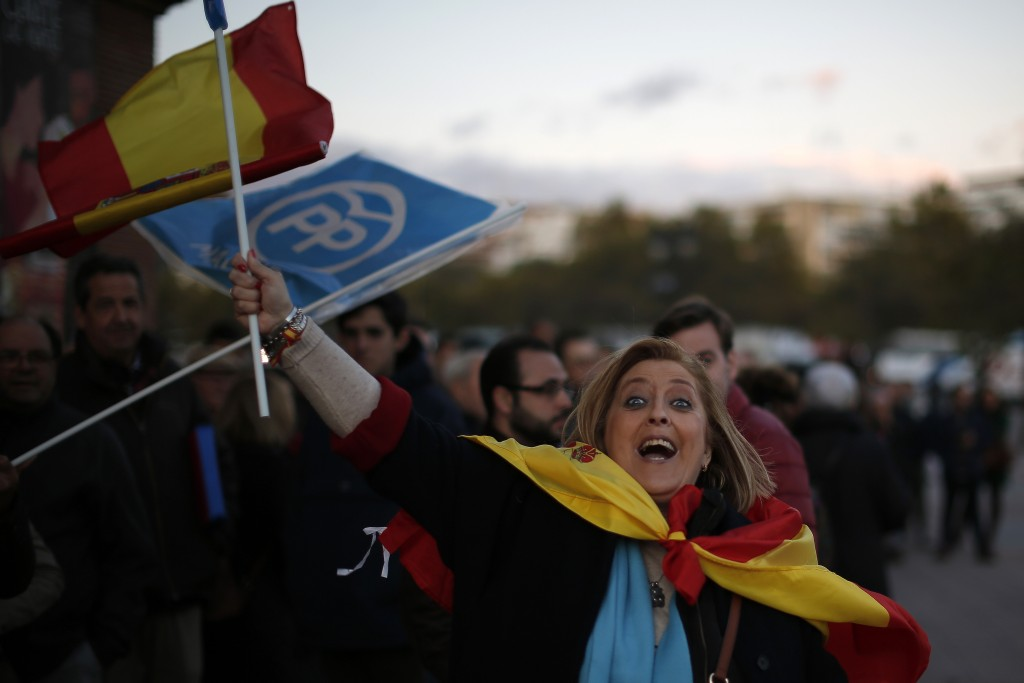A woman waves a Spanish flag before the Popular Pa...