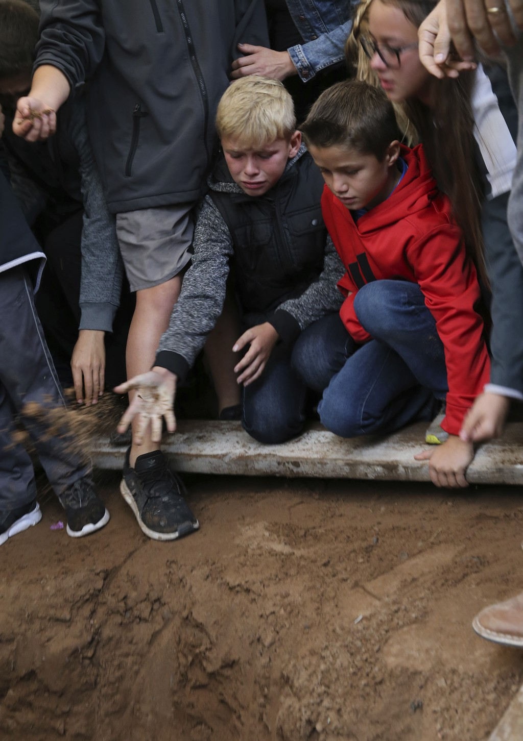 A child tosses a handful of dirt on the coffin that contains the remains of 12-year-old Howard Jacob Miller Jr., at the cemetery in Colonia Le Baron, ...