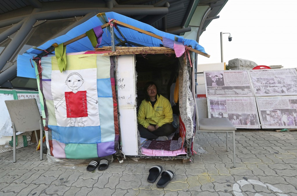 In this April 2, 2019, photo, Choi Seung-woo, a victim of Brothers Home, sits in a tent near the National Assembly in Seoul, South Korea. Choi and a s...