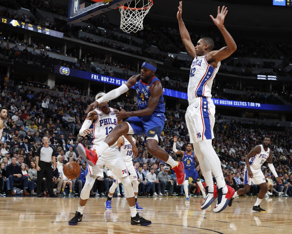 Denver Nuggets forward Paul Millsap, left, loses control of the ball while driving to the rim past Philadelphia 76ers forwards Tobias Harris, back lef...