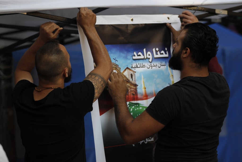 "In this Thursday, Nov. 7, 2019, Shiite anti-government protesters install an Arabic placard that reads, "" We are one, Lebanon without sectarianism,"" i..."