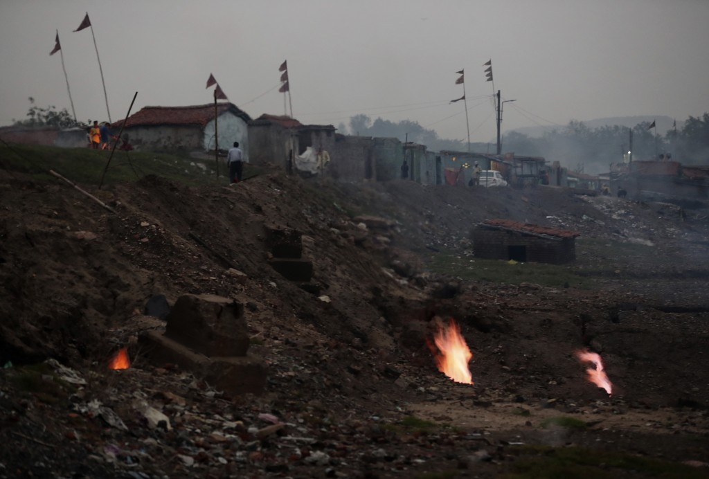 In this Oct. 23, 2019, photo, flames rise out of the fissures on the ground above coal mines in the village of Liloripathra in Jharia, a remote corner...
