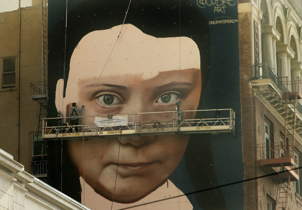 Andres Petreselli paints a mural on the side of a building depicting Swedish teen climate activist Greta Thunberg, Friday, Nov. 8, 2019, in San Franci...