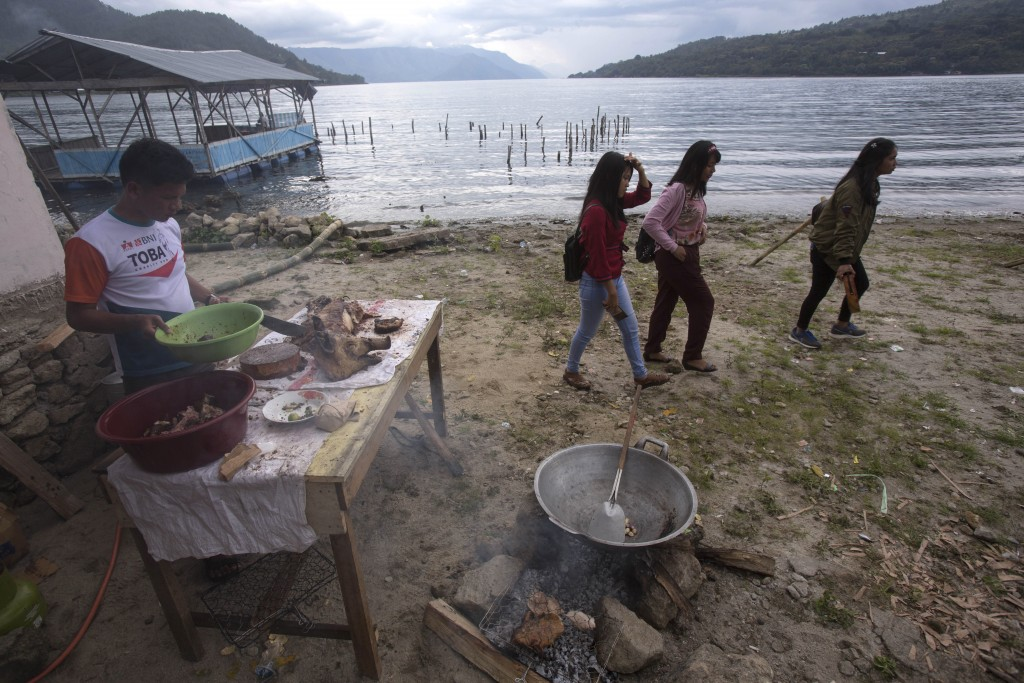 In this Saturday, Oct 26, 2019, photo, visitors walk past a man cooking pork by Lake Toba during Toba Pig and Pork Festival in Muara, North Sumatra, I...