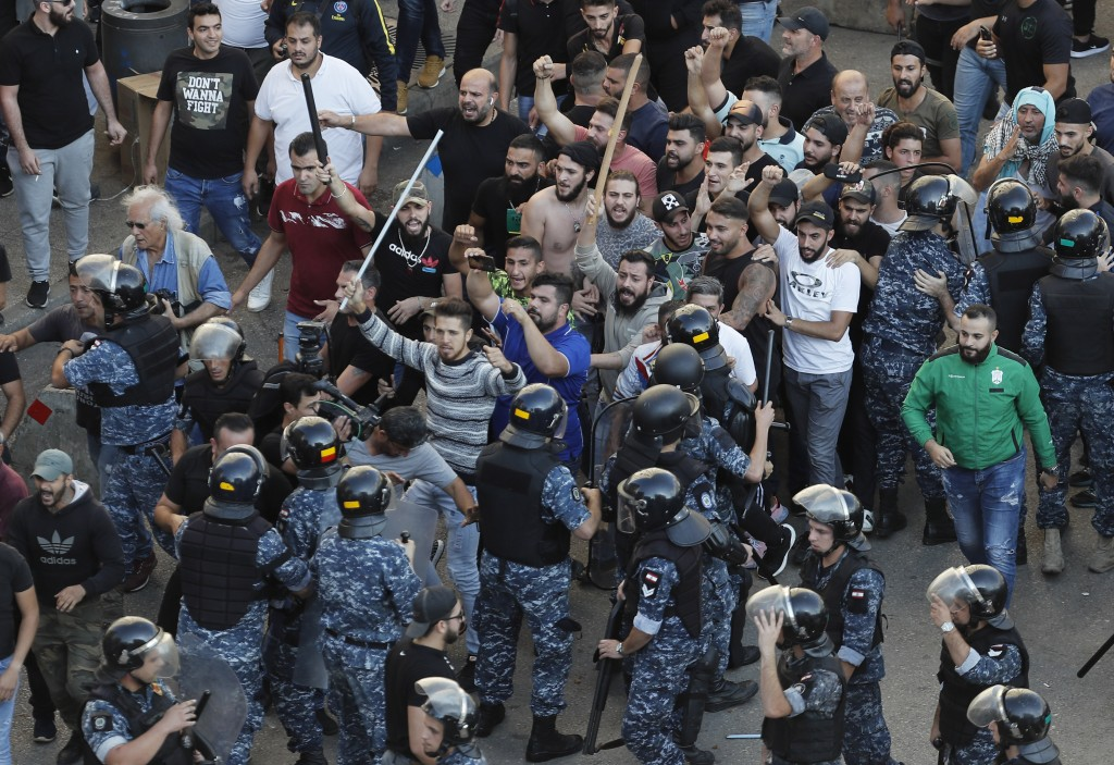 FILE - In this Tuesday, Oct. 29, 2019 file photo, riot police try to stop supporters of the Shiite Hezbollah group who arrived to burn and destroy ten...