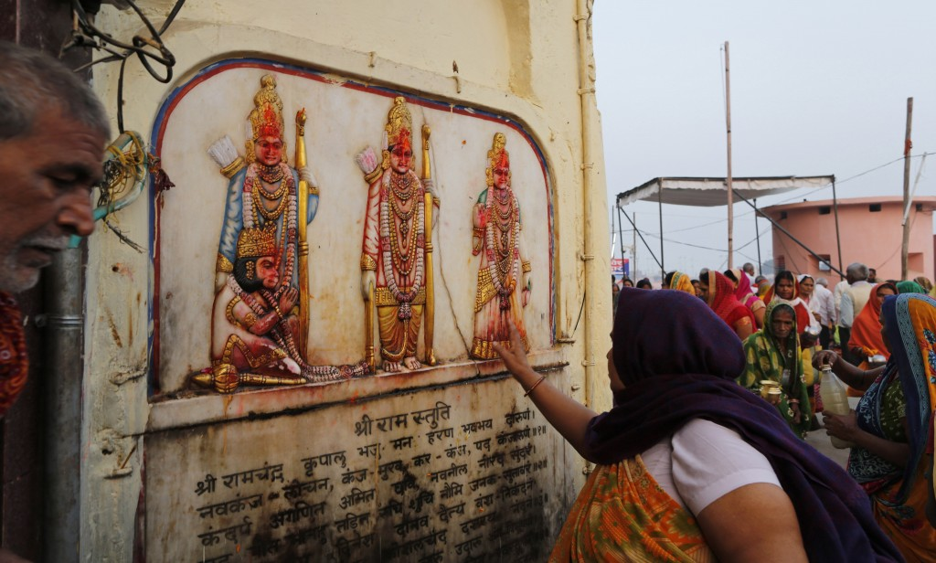 A Hindu pilgrim touches in obeisance an image of Hindu deities Rama, Sita and Lakshman in Ayodhya, India , Saturday, Nov. 9, 2019. India's security fo...