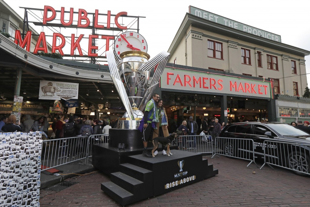 Fans wearing Seattle Sounders gear pose for a photo with a giant replica of the MLS Cup trophy, Friday, Nov. 8, 2019, at Pike Place Market in Seattle....