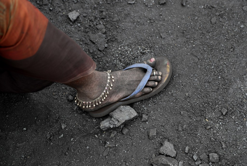 In this Oct. 23, 2019, photo, a laborer sports an anklet as she takes a break from loading coal into trucks for transportation in the village of Godha...