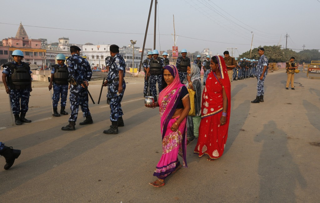 Hindu pilgrims walks past security officers standing guard in Ayodhya, India , Saturday, Nov. 9, 2019. India's security forces were on high alert ahea...