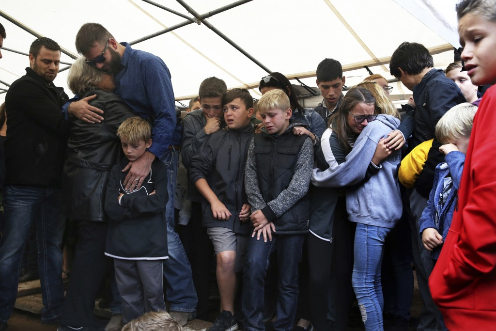 Howard Miller embraces family members during the burial service for his wife Rhonita Miller and four of their young children who were murdered by drug...