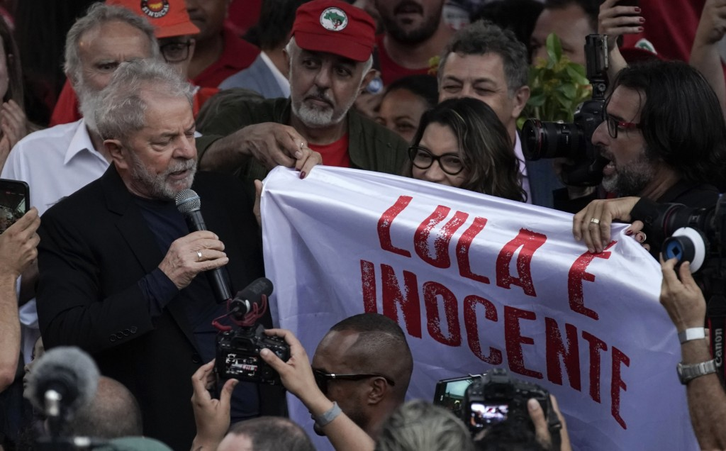 """Brazil's former President Luiz Inacio Lula da Silva holds the corner of a banner that reads in Portuguese """"Lula is innocent"""" as he speaks to supporter..."""
