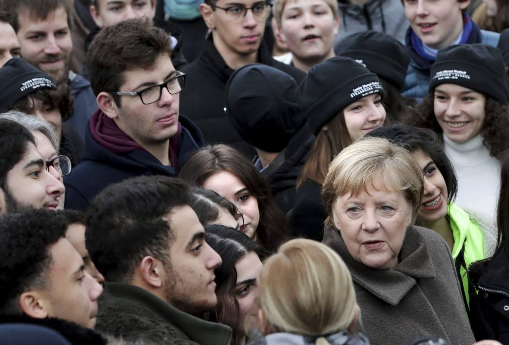 German Chancellor Angela Merkel, right, poses for a photo with visitors prior to a memorial service in the chapel at the Berlin Wall Memorial in Berli...
