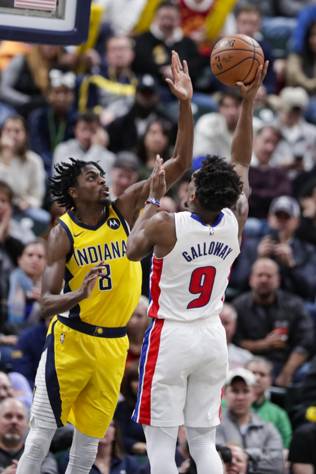 Indiana Pacers forward Justin Holiday (8) blocks the shot of Detroit Pistons guard Langston Galloway (9) during the second half of an NBA basketball g...