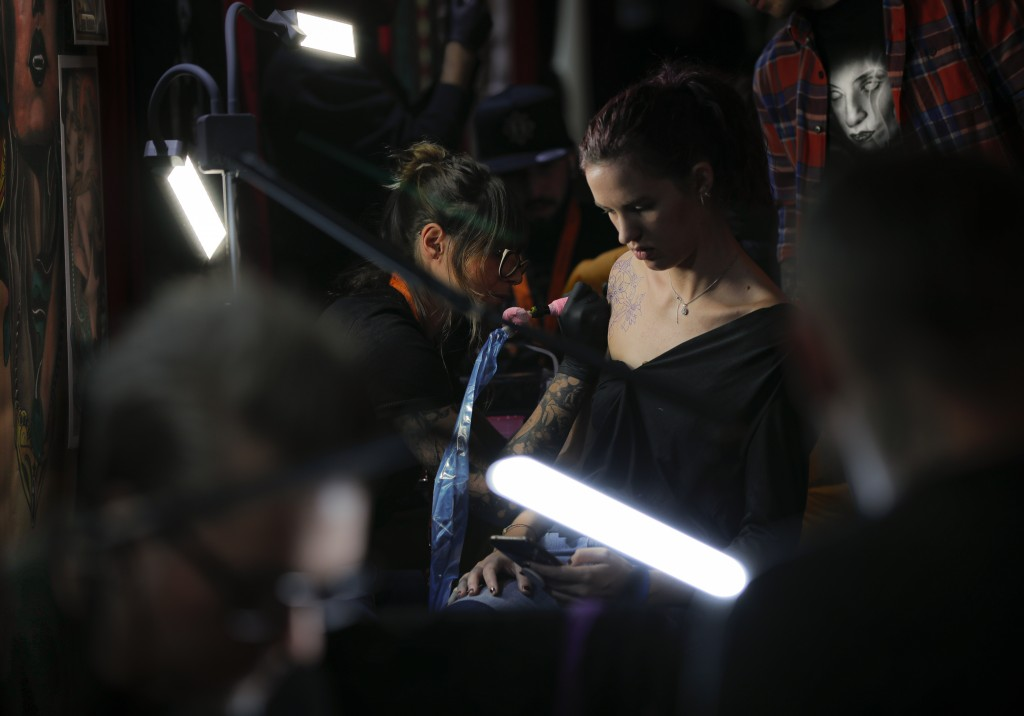 In this Saturday, Nov. 2, 2019, a woman gets a tattoo done during the 10th International Tattoo Convention in Bucharest, Romania. The three-day event ...