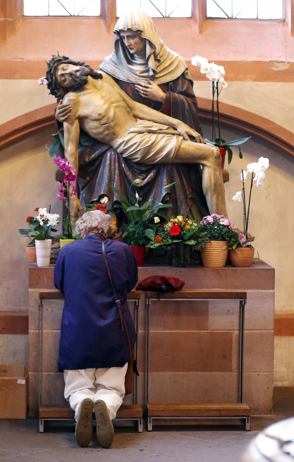 FILE - In this Sept. 27, 2012, file photo, a woman prays under a statue depicting Jesus and Mary, in the cathedral of Frankfurt, Germany. Catholics in...