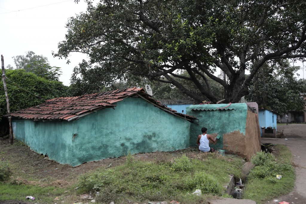 In this Oct. 23, 2019, photo, a villager paints his house in preparation of Diwali, a Hindu festival, in the village of Bastakola involved in coal min...