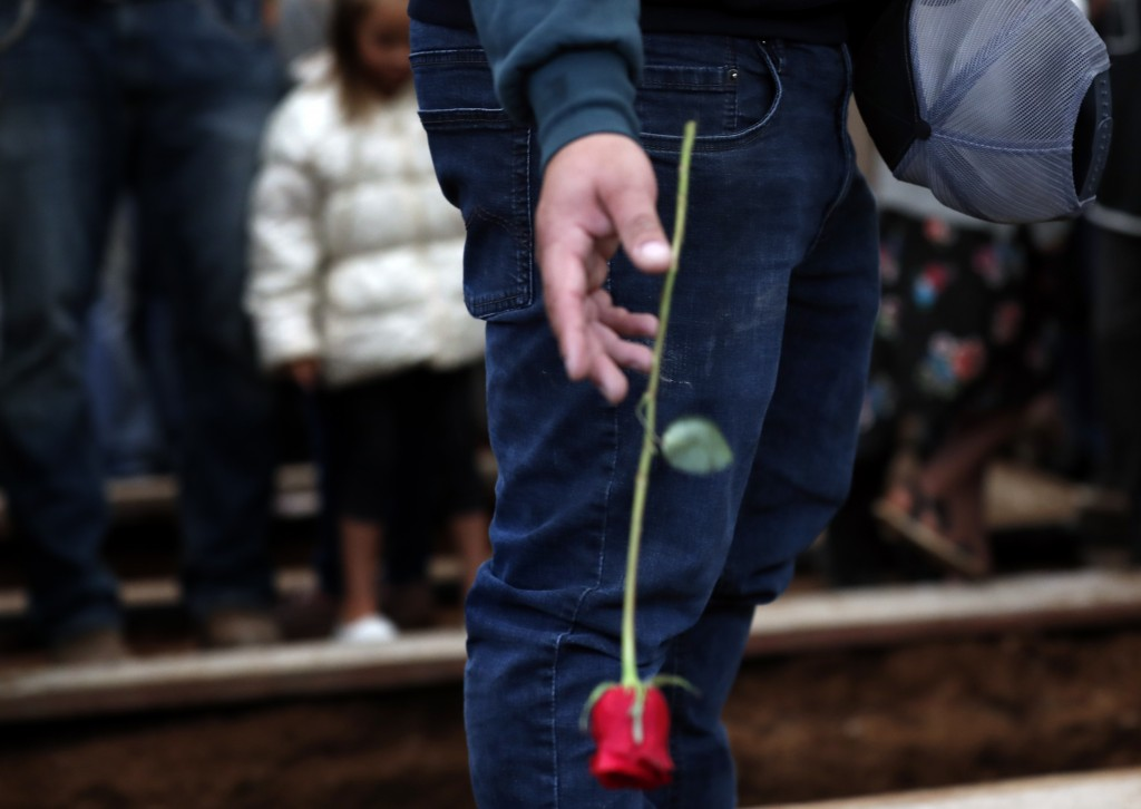 A mourner drops a red rose into a freshly dug grave at the cemetery in Colonia Le Baron, Mexico, Friday, Nov. 8, 2019, during the burial service for R...