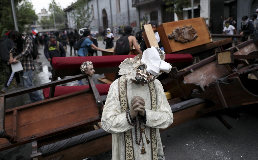 A damaged statue taken from a church forms part of barricade created by antigovernment protesters, in Santiago, Chile, Friday, Nov. 8, 2019.  Chile's ...