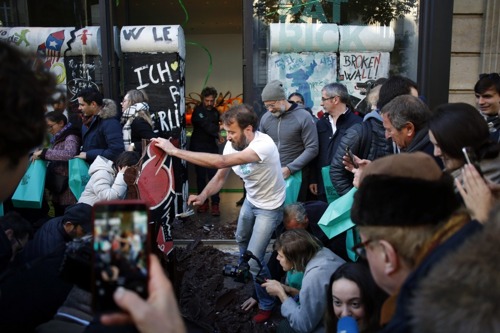 French chocolate maker Patrick Roger, center, destroys a reproduction of the Berlin wall in chocolate, to mark the 30th anniversary of the fall of the...