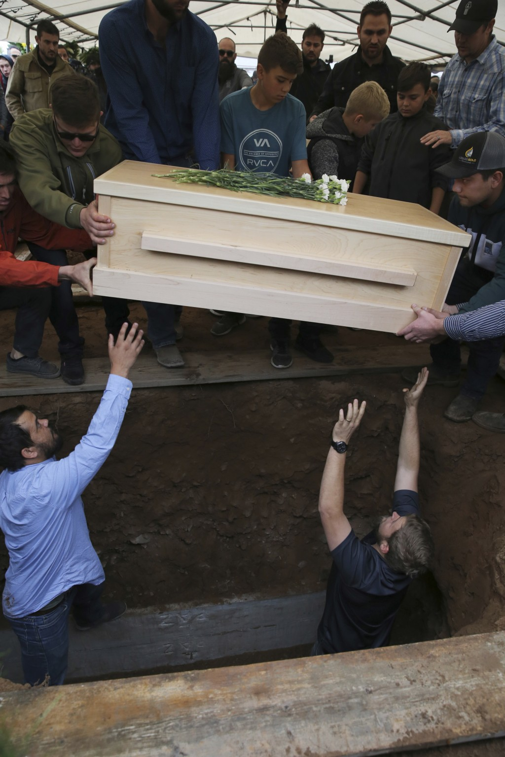 The coffin that contains the remains of 12-year-old Howard Jacob Miller Jr. is lowered into a grave at the cemetery in Colonia Le Baron, Mexico, Frida...