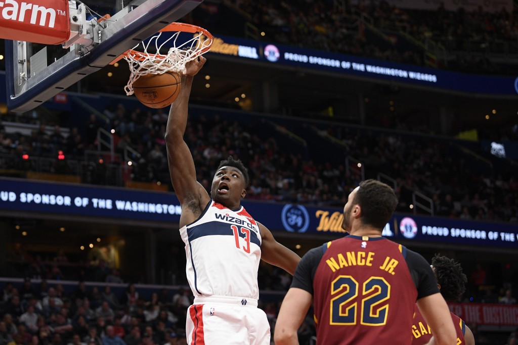 Washington Wizards center Thomas Bryant (13) dunks past Cleveland Cavaliers forward Larry Nance Jr. (22) during the first half of an NBA basketball ga...