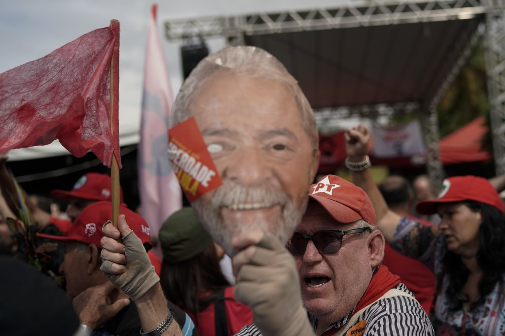 A supporter of Brazil's former President Luiz Inacio Lula da Silva holds up a mask of Da Silva outside the Federal Police headquarters where the forme...