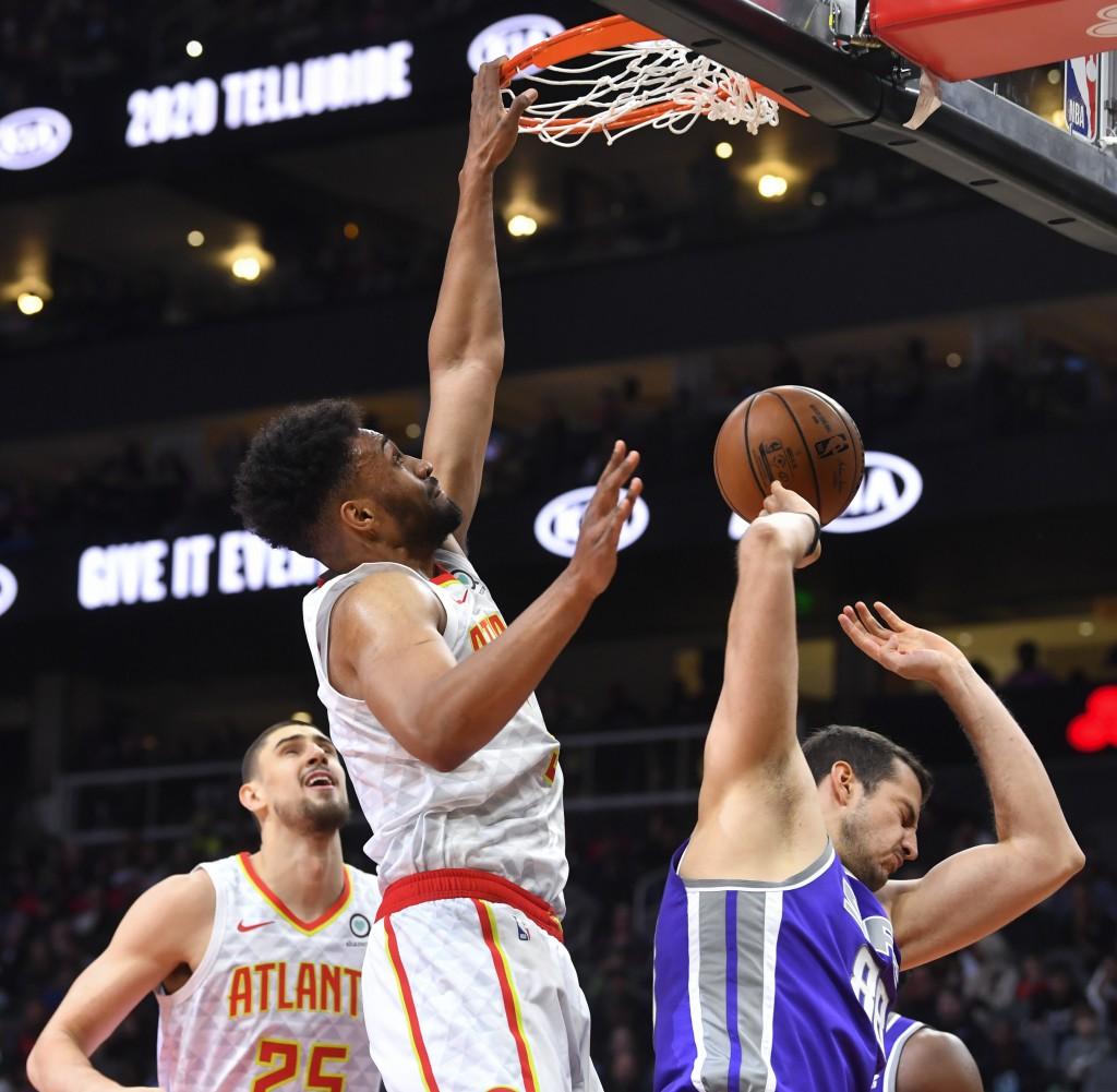 Atlanta Hawks forward Jabari Parker dunks against Sacramento Kings forward Nemanja Bjelica, right, of Serbia, during the first half of an NBA basketba...