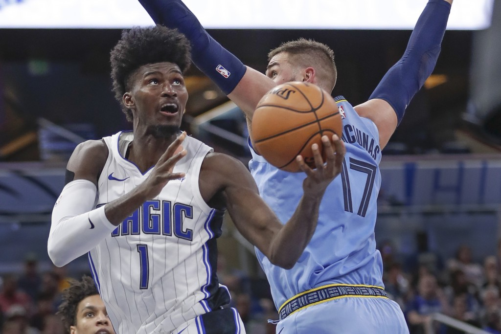 Orlando Magic's Jonathan Isaac (1) draws a foul from Memphis Grizzlies' Jonas Valanciunas (17) as he goes up to shoot during the first half of an NBA ...